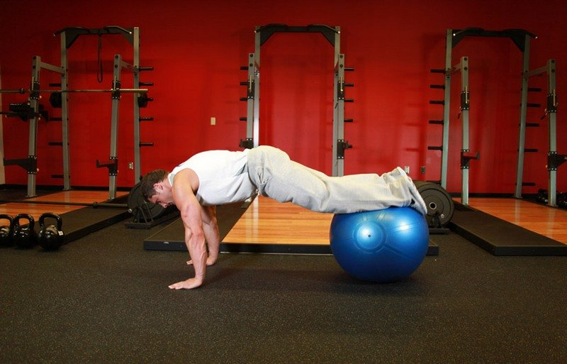 Планка на фитболе с подтягиванием колен к груди