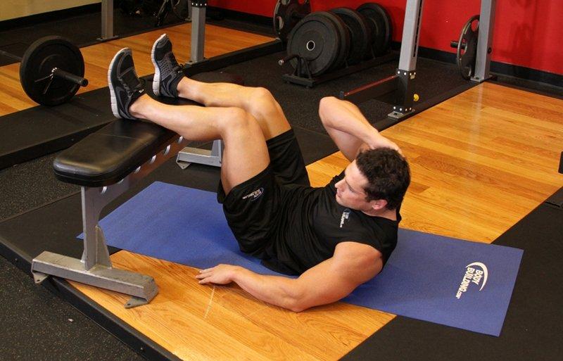 Косые скручивания с ногами на скамье